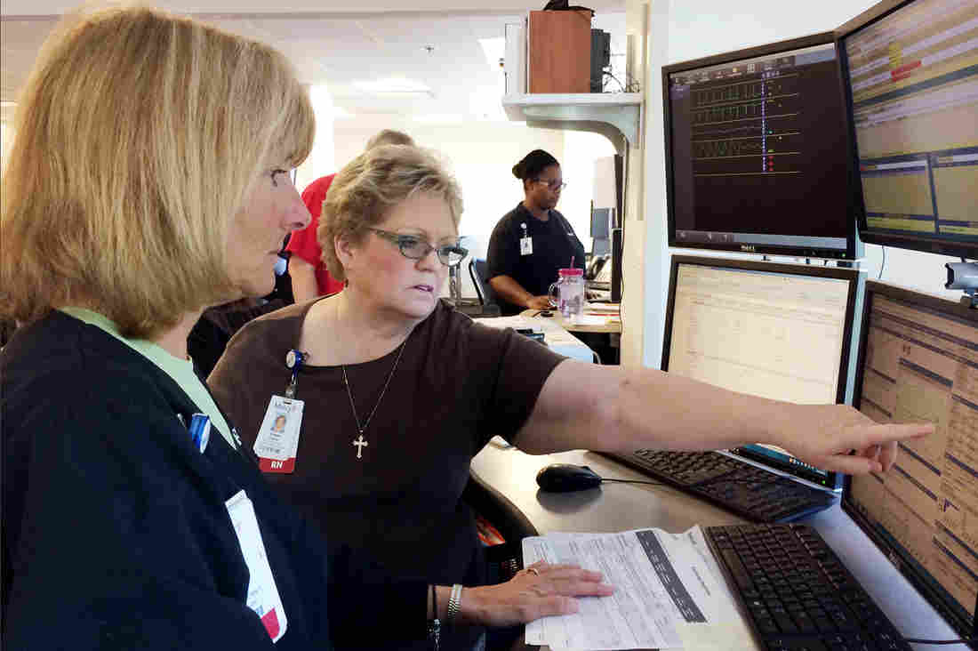 Nurses Patricia Wegener (left) and Susan Davis at Mercy Hospital can monitor the condition of a patient who is miles away via the hospital's technology. But some health insurers and analysts remain skeptical that telemedicine saves money.